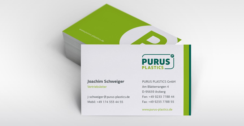 Zu sehen ist ein Stapel Visitenkarten der Firma Purus Plastics. Der Stapel zeigt die Rückseite der Karte an, während eine senkrecht aufgestellte und an den Stapel angelehnte Karte die Vorderseite der Visitenkarte in Richtung Bildbetrachter zeigt.