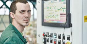 Angestellter vor einer Maschine der Firma PURUS PLASTICS