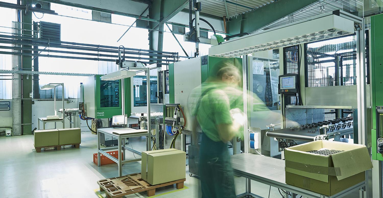 Ein Angestellter an einer Maschine in der Firma PURUS PLASTICS